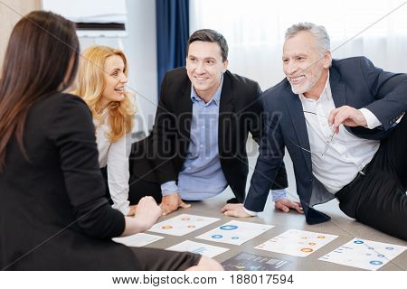 Positive mood. Happy nice delighted men sitting opposite their colleague and looking at her while doing a team building activity together