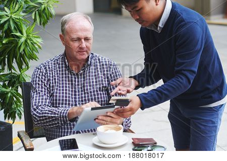 Waiter asking mature man to insert information for payment