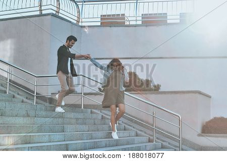She is everything to him. Full length of handsome man and young attractive woman holding hands while walking down the stairs outdoors
