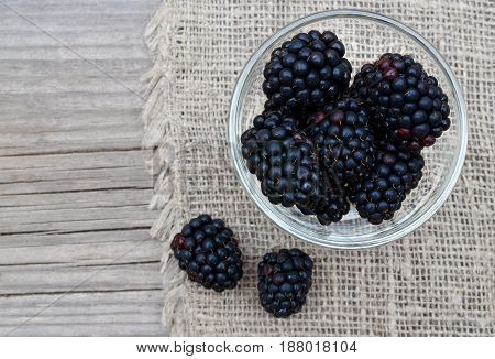 Ripe blackberries in a glass bowl on burlap cloth on old wooden background.Blackberry.Healthy food or diet concept.