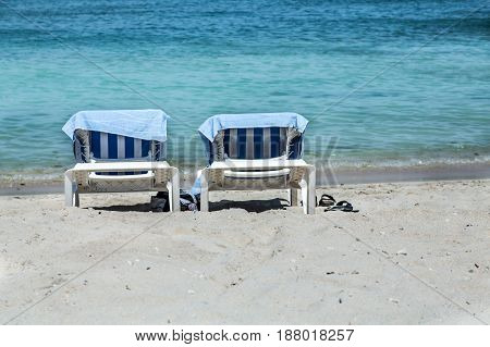 Two chaise lounges on a Caribbean beach with blue towels