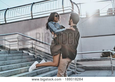 Falling in love. Handsome man carrying young attractive woman while spending time outdoors