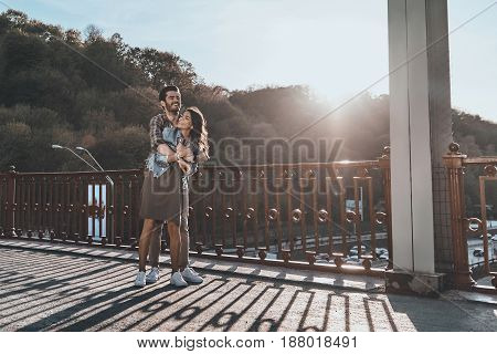 Happy to be together. Full length of beautiful handsome man embracing young attractive woman while standing on the bridge outdoors