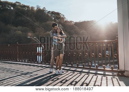 Best date. Full length of handsome man embracing young attractive woman while standing on the bridge outdoors