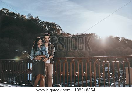 Spending nice day together. Handsome man embracing his girlfriend while walking by the bridge