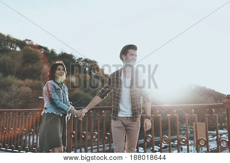 Enjoying nice day together. Beautiful young couple holding hands and smiling while standing on the bridge outdoors