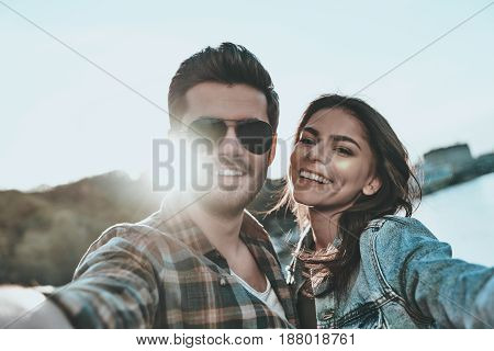Selfie with sweetheart. Self portrait of beautiful young couple embracing and looking at camera while standing on the bridge outdoors