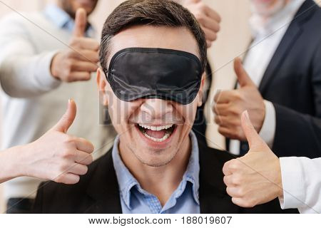 Absolute darkness. Joyful positive pleasant man smiling and wearing a sleeping mask while being cheered up by his colleagues