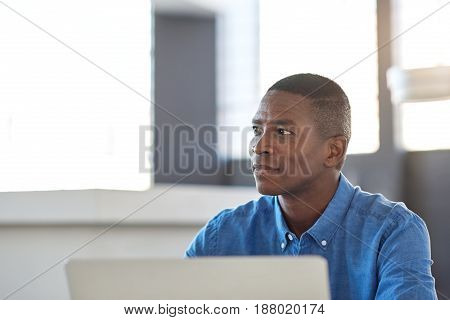 Smiling African businessman sitting at his desk in a large modern office working on a laptop looking deep in thought