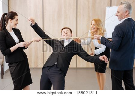 Fun in the office. Delighted positive nice people standing opposite each other and holding the rope while looking at their colleague