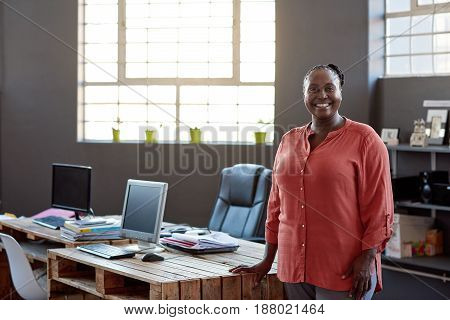 Portrait of a casually dressed young African businesswoman smiling confidently while standing alone by her desk in a modern office