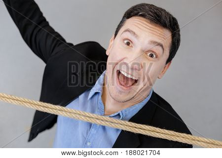 Happy face. Portrait of a happy emotional handsome man smiling and looking at you while going under the rope