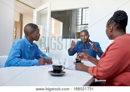 Focused young African businessman explaining business concepts while having a meeting with colleagues at a table in a modern office