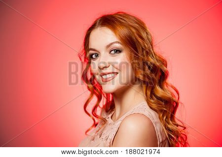 Pretty girl looking at camera and smiling, red studio background, beauty photo