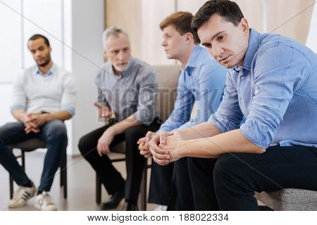 Psychological therapy. Handsome sad young man thinking about his problems and being depressed while being on a psychological session