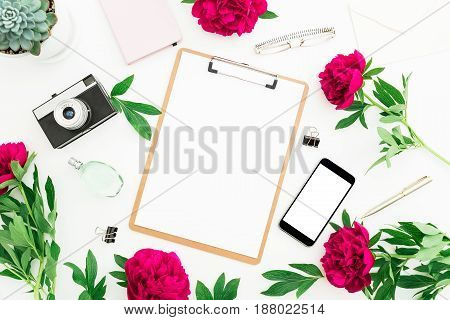 Blogger or freelancer workspace with clipboard, notebook, retro camera, peonies and mobile phone on white background. Flat lay, top view.