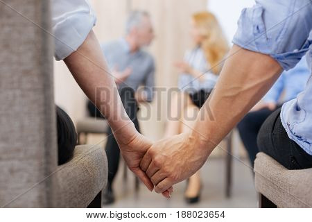Not alone. Nice pleasant positive people sitting together and holding their hands while shoeing their unity