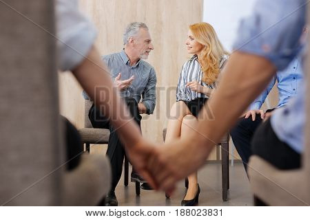 Interesting conversation. Pleasant nice elderly man sitting together and smiling while having a conversation