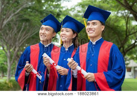 Confident Vietnamese graduates with diplomas in hands standing in row and looking to future with optimism, waist-up portrait