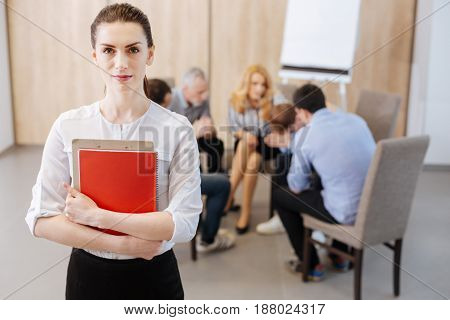 Professional treatment. Confident nice professional psychologist standing in front of her group and looking at you while having a group therapy session