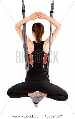 Young woman doing anti-gravity aerial yoga in hammock on white background.