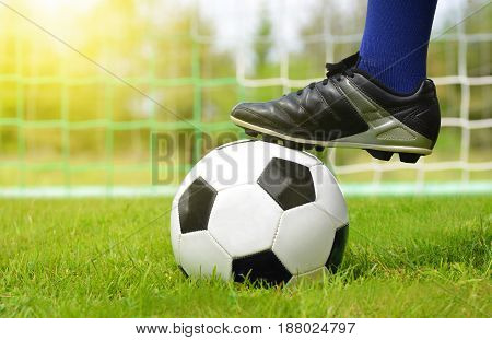 Soccer ball and foot of football player. The beginning of the game.