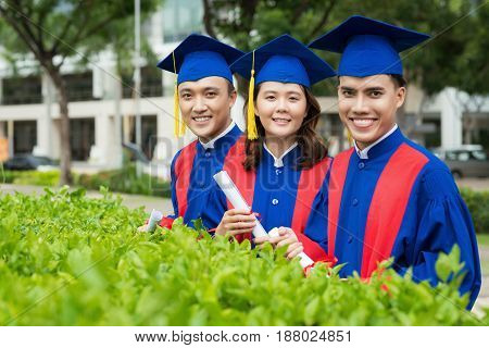 Smiling Vietnamese students in graduation gowns posing for photography in university campus, waist-up portrait