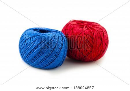 red and blue color of balls of cotton threads for knitting on a white background