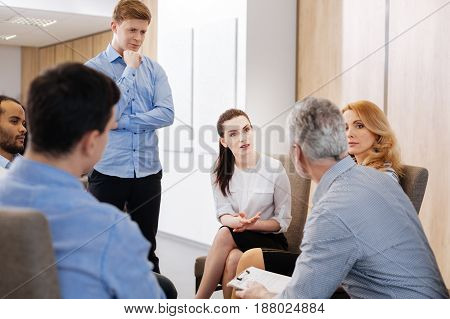 Interesting discussion. Handsome nice thoughtful man standing near his colleagues and looking at them while listening to their group discussion