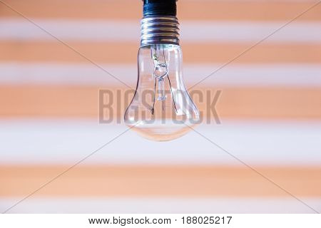 Light bulb close-up on a light orange striped background
