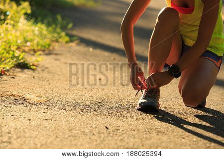 Young fitness woman runner tying shoelace on morning tropical forest trail