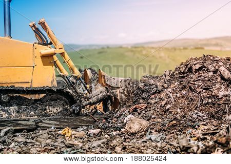 Industrial Bulldozer Leveling Garbage Grounds. Heavy Duty Machinery Working On Construction Site