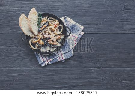 Seafood Stew in Saucepan. Authentic italian restaurant cuisine, healthy food. Oysters, shrimps, calamari in white cream with bruschetta. Bowl on dark black wood background, top view