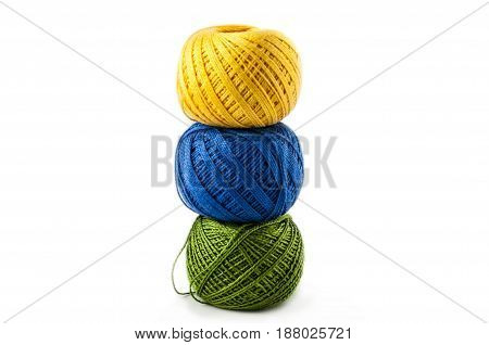 yellow blue green balls of cotton threads for a knitting on a white background