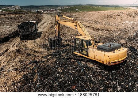 Excavator And Dumper Truck Working On Modern Garbage Construction Site