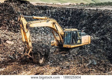 Industrial Details Of Garbage Dump. Heavy Duty Excavator Digging And Loading Urban Trash