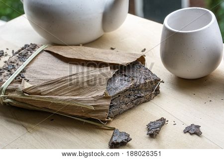 Big pack of black natural tea with one cup and teakettle on the wooden background