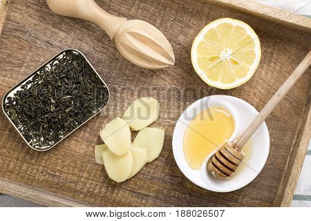 Ingredients for ginger tea. Green tea ginger lemon and honey on a wooden tray. Top view.