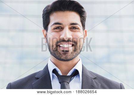 Portrait of a serious smiling happy successful arabic businessman or worker in black suit with tie and shirt with beard standing in front of an office building.