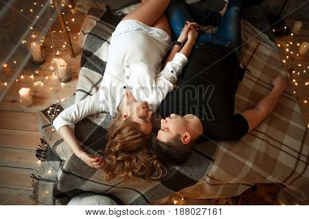 Pregnant woman with her husband lies on bed and holds his hand. Around them on floor are glowing lights and burning candles.