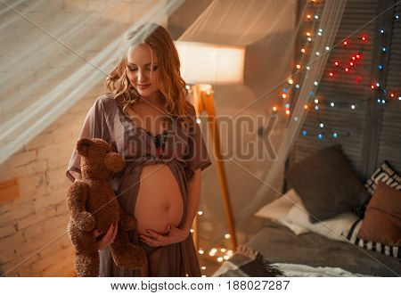 Pregnant woman with teddy bear in open peignoir hugs her belly. View through transparent curtain. Around are visible light floor lamp and pillows on bed.