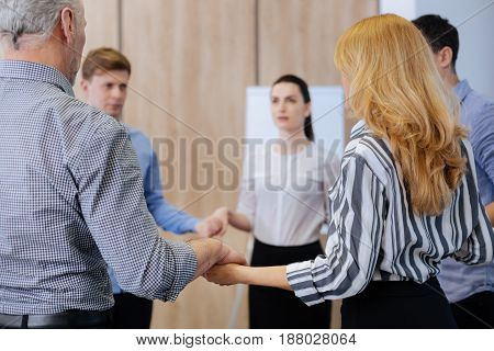 In the circle. Nice serious adult people standing in the circle and holding hands while showing their unity