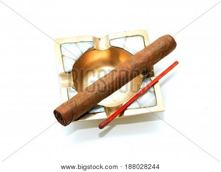 One Cuban cigar on vintage brass ashtray against white background
