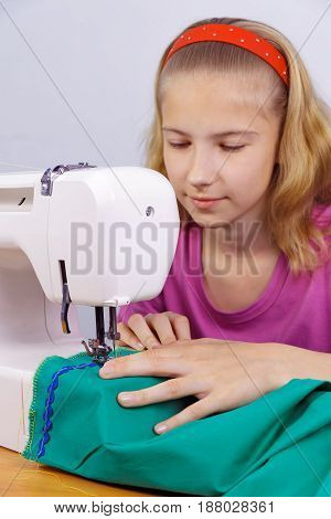 Girl learns to sew on an electric sewing machine