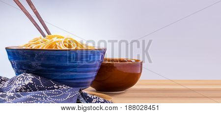 cooked Japanese wheat noodles in a blue ceramic bowl with wooden chopsticks on wooden table room for copy space
