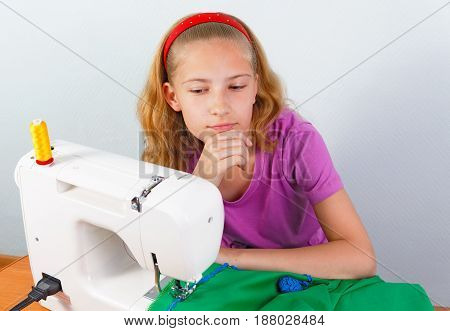 Girl teenager comes up with a new model of sewing clothes on a sewing machine