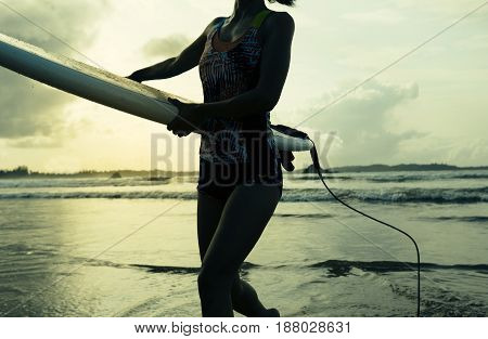 young woman surfer with surfboard walking on beach