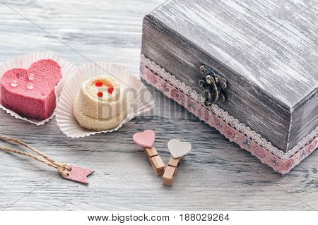 Pink cake heart with an old box.Dessert with delicate cream