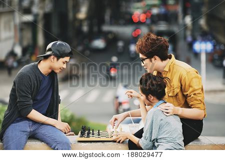 Lovely Asian couple and their male friend playing chess while sitting on bridge railing, busy city center on background