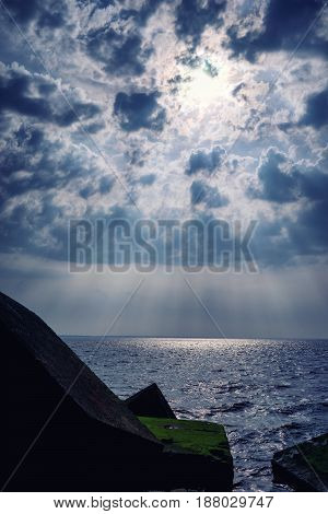 Concrete protective blocks against the sun's rays through the clouds over the sea